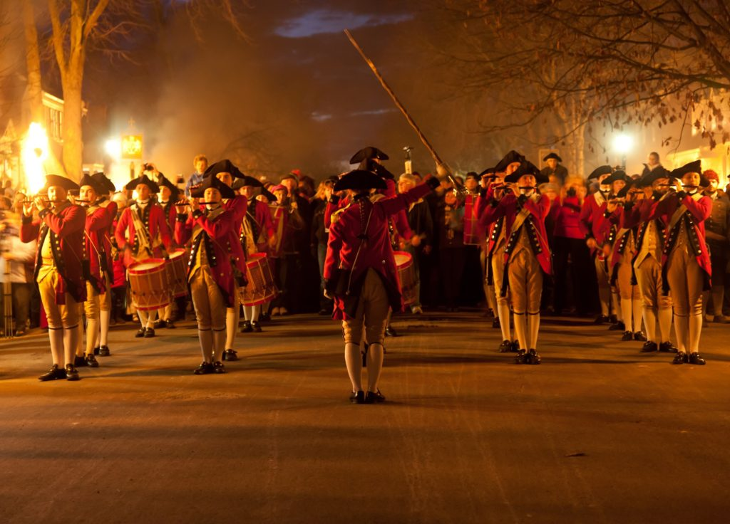"""Williamsburg, VA, USA - December 29, 2011: Red-coated fife and drum corps take part in the Illumination of the Taverns parade in Colonial Williamsburg. The Grand Illumination takes place on the first Sunday in December."""